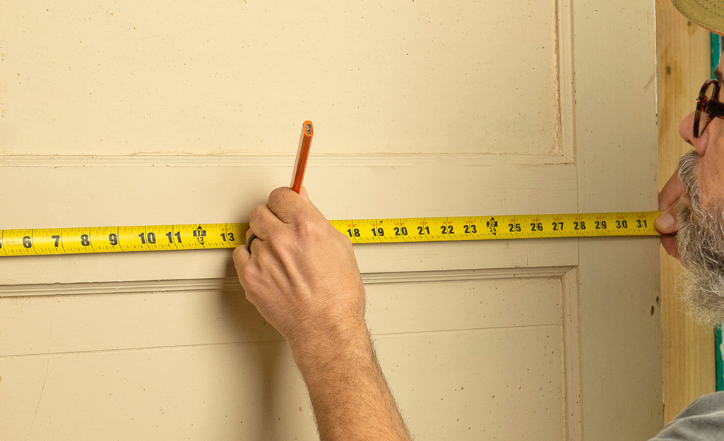 A man uses a tape measure to measure and mark for the peephole.