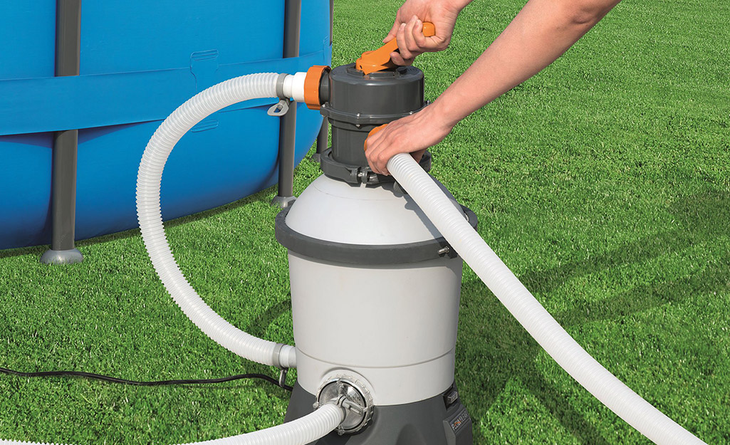 A person assembles a sand pool filter.