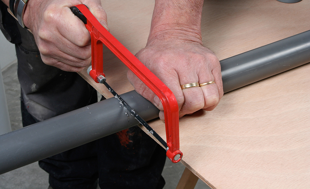 A person cuts PVC pipe with a hacksaw.