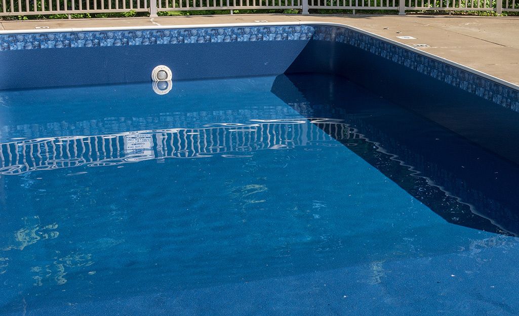 A close up of the inside of a pool in a backyard