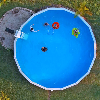 An aerial view of an above-ground pool in a backyard