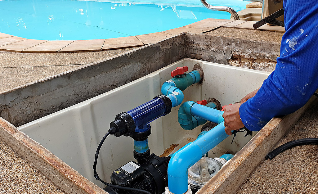 A person opens the cover of a pool pump.