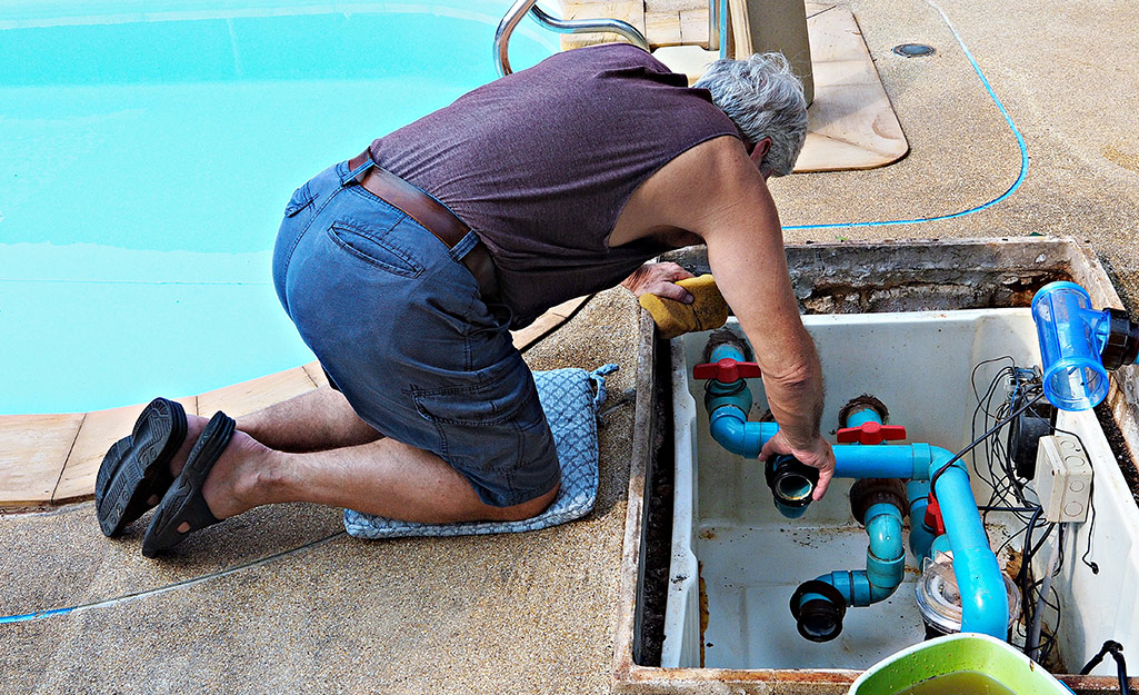 A person adds new fittings for replacing a pool pump.