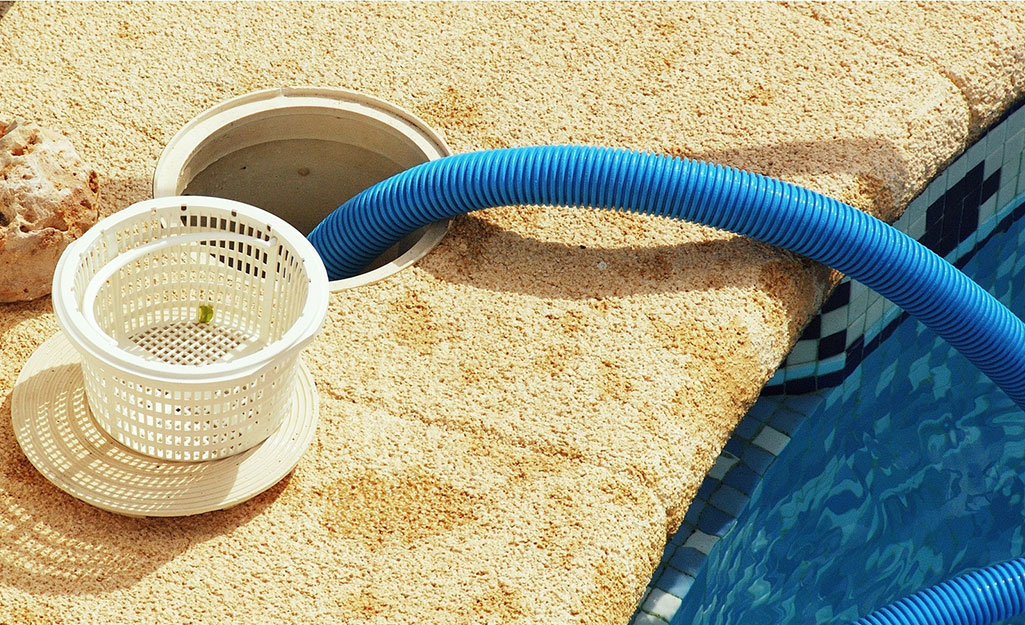 A clean filter sits on the edge of a pool near the pump access.