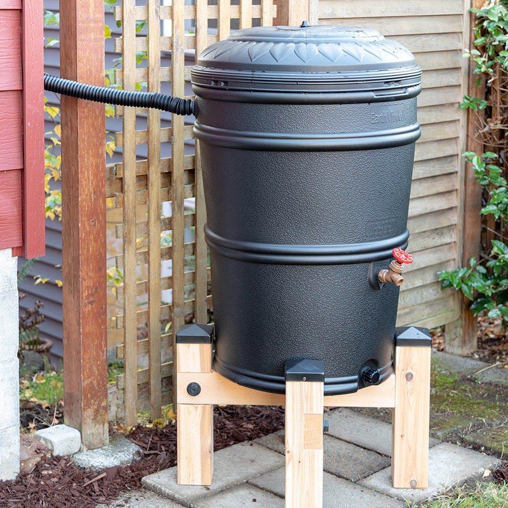 An elevated rain barrel sits outside.