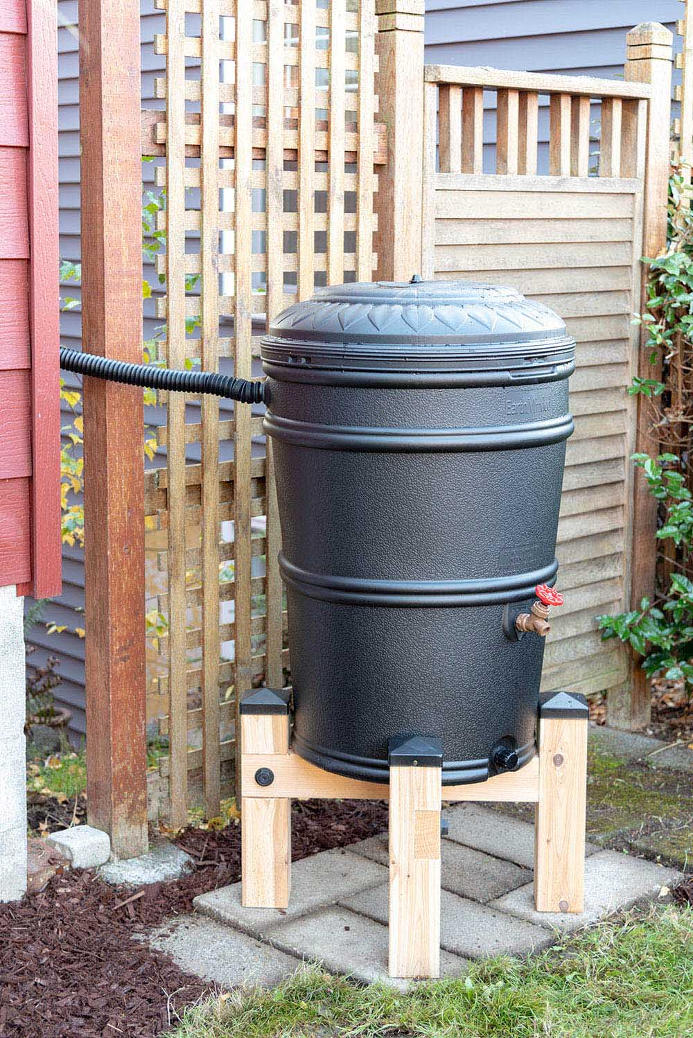A black rain barrel is elevated on a wooden stand.
