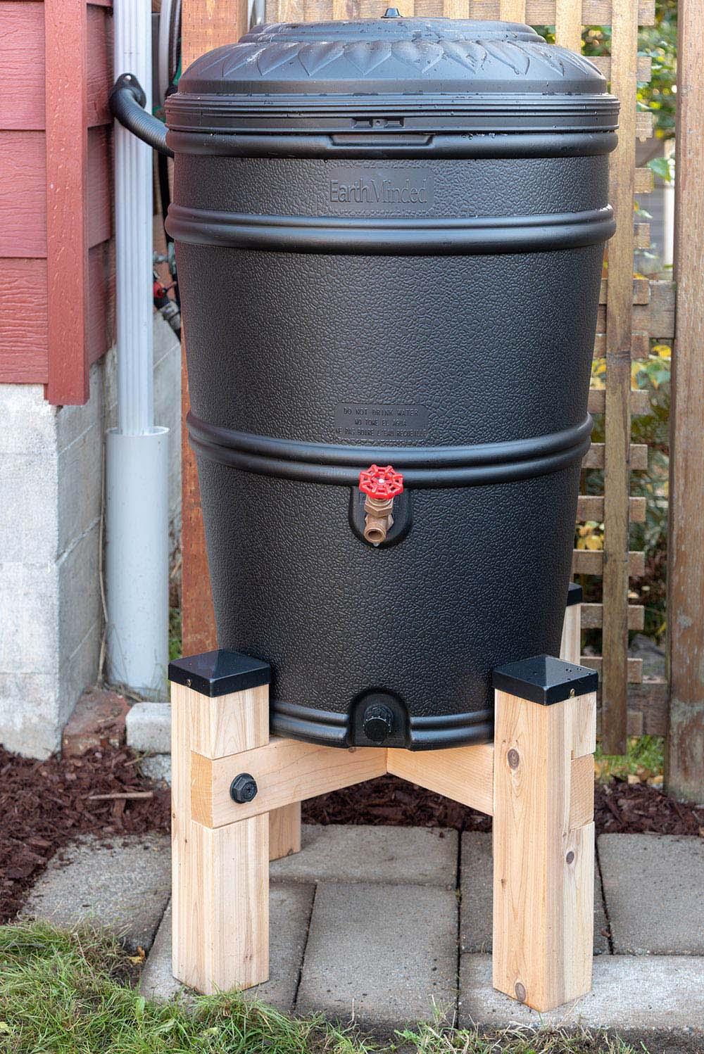 A installed black rain barrel sitting on a wooden stand.