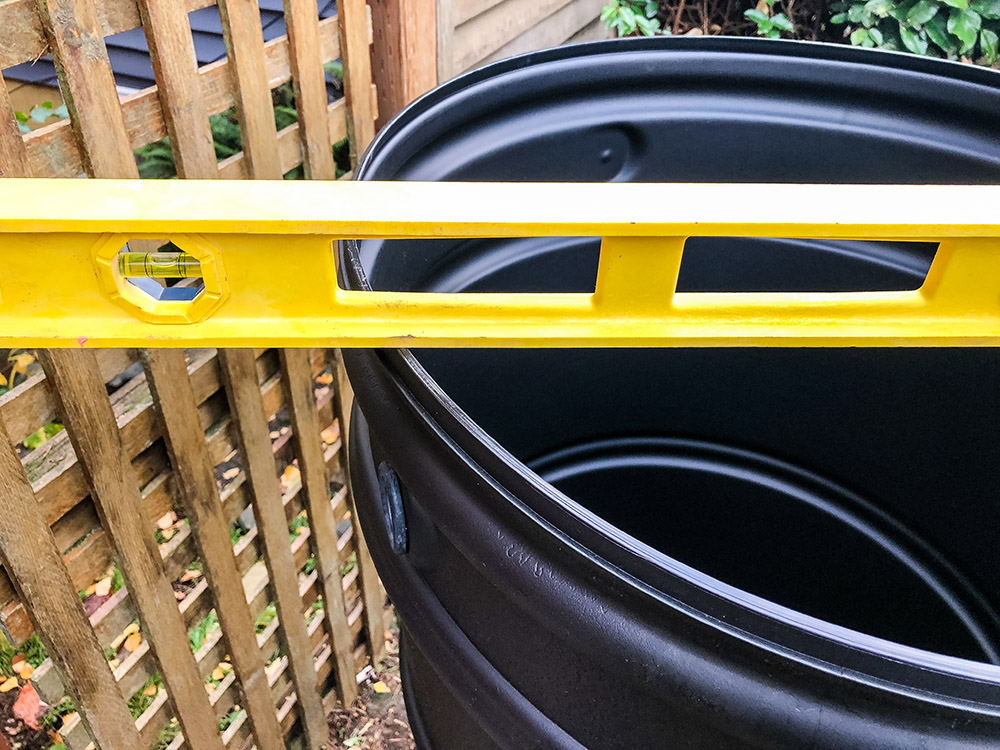 A yellow level sits on top of a black rain barrel.