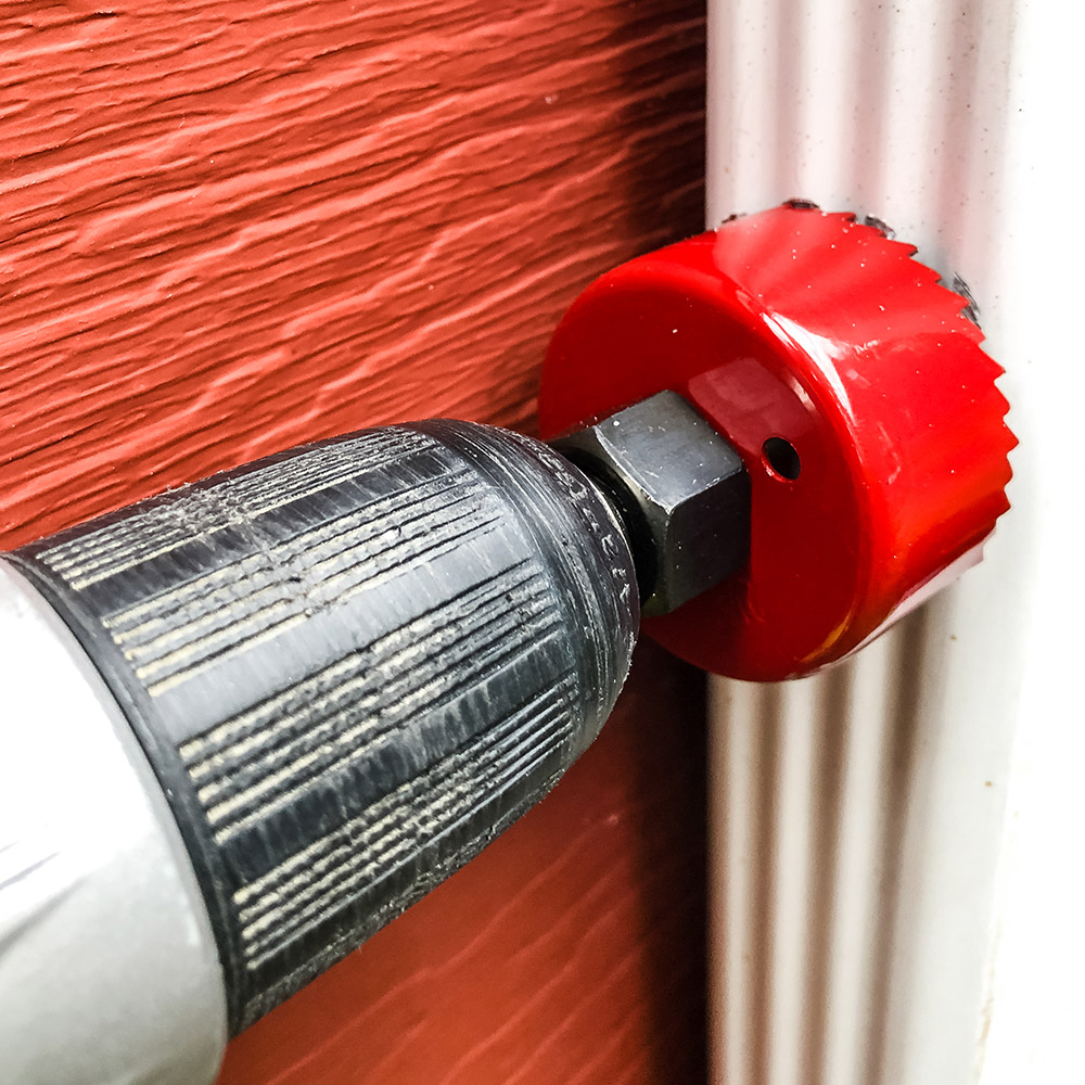 A red hole saw drilling into a downspout.