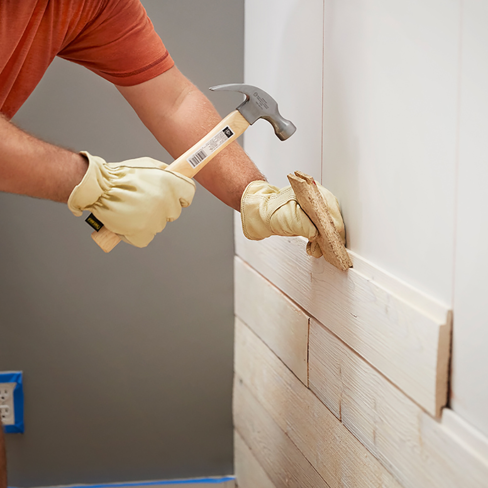 A person holding a hammer and tapping block up to a piece of shiplap on a wall.