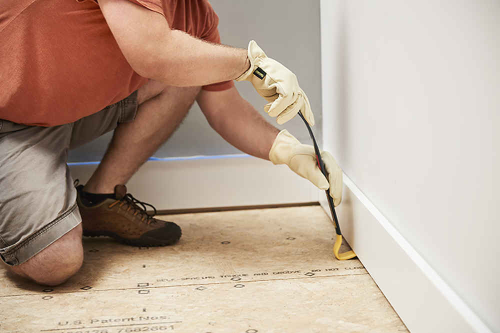 A person using a pry bar to remove a baseboard.
