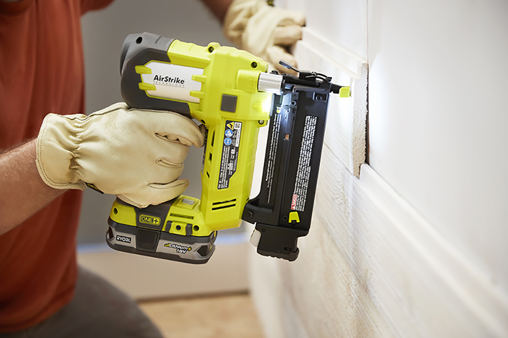 A person attaching shiplap to a wall with a cordless finish nailer.
