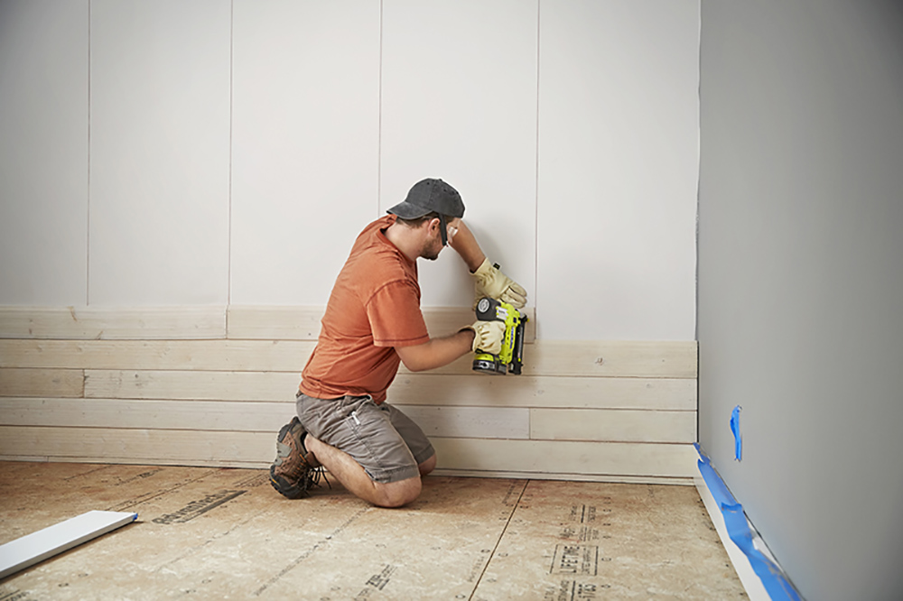 A man attaching shiplap boards to a wall.