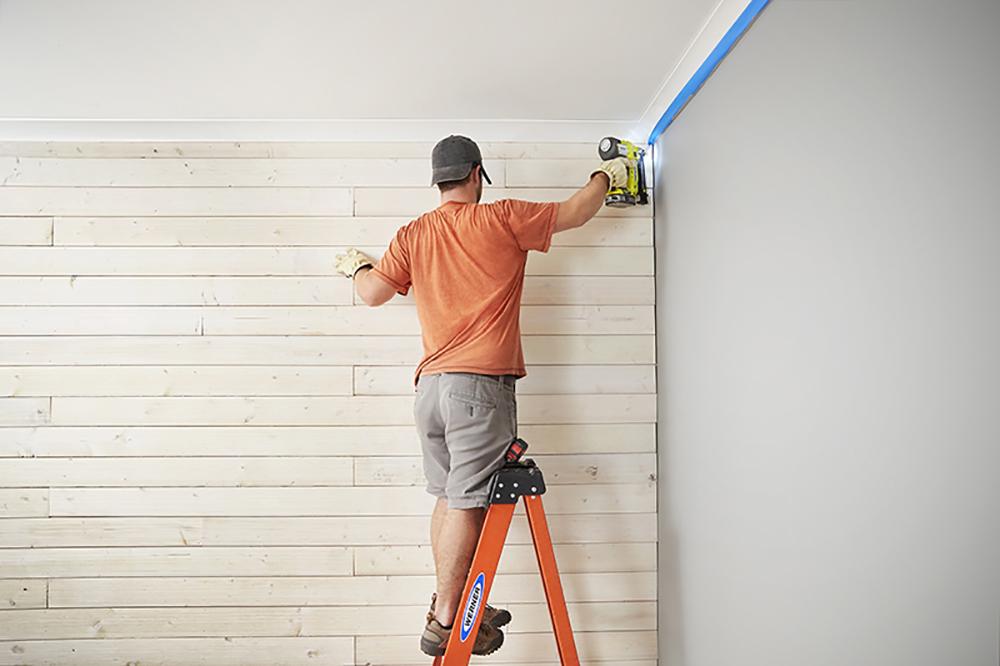 A man standing on a ladder finishing a shiplap wall.