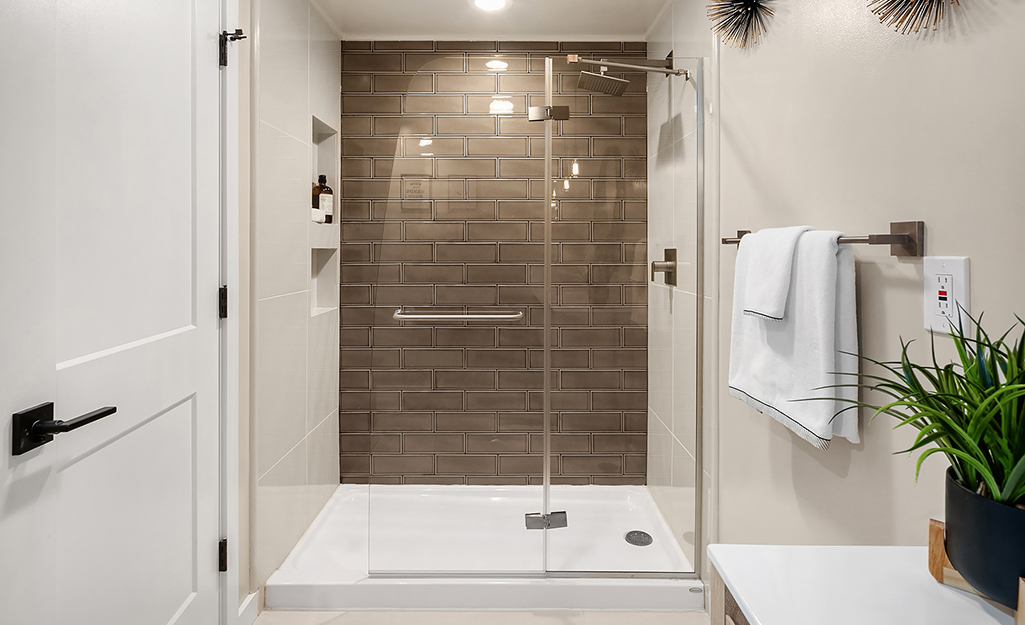 A walk-in shower with glass doors and fiberglass shower pan.