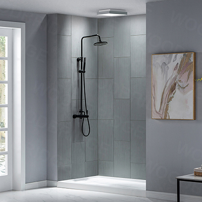 A walk-in shower with gray tile and fiberglass shower pan.