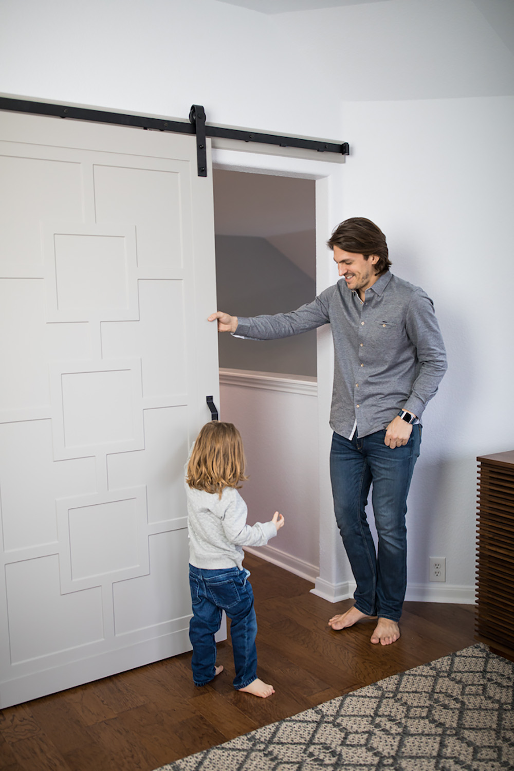 Two people standing in front of a sliding barn door