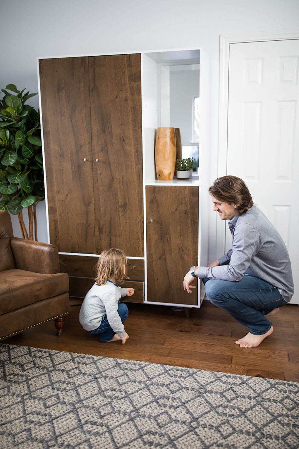 A person and child squatting on the floor looking at a cabinet
