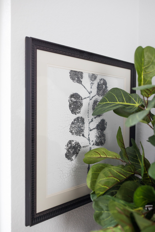A framed art behind a green plant