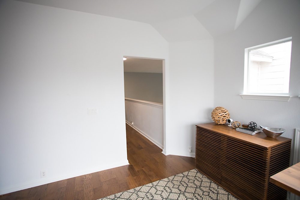 A shot of a blank wall with a door opening on the right side