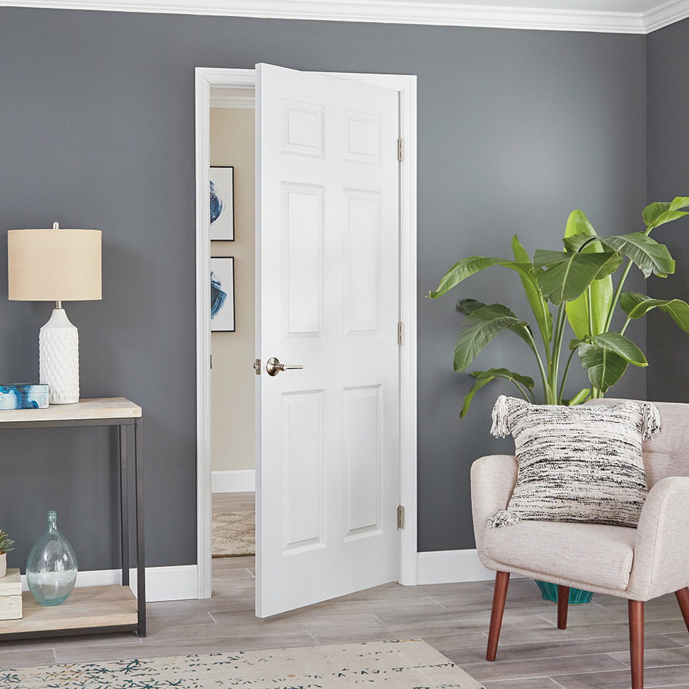 A white split-jamb door inside a home with grey walls.