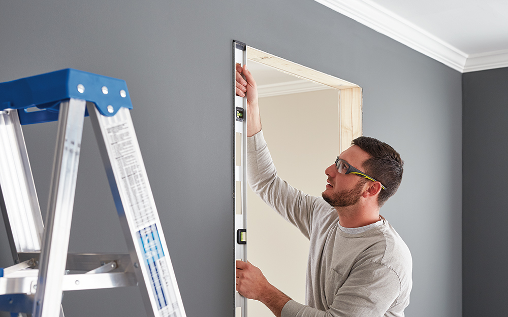 A man using a level to ensure a door frame is straight.