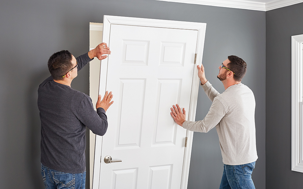Two men placing a door into an open frame.