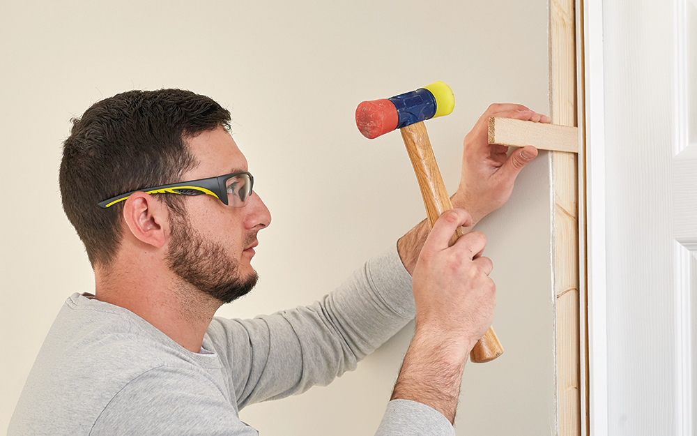 A man securing shims into the door frame.