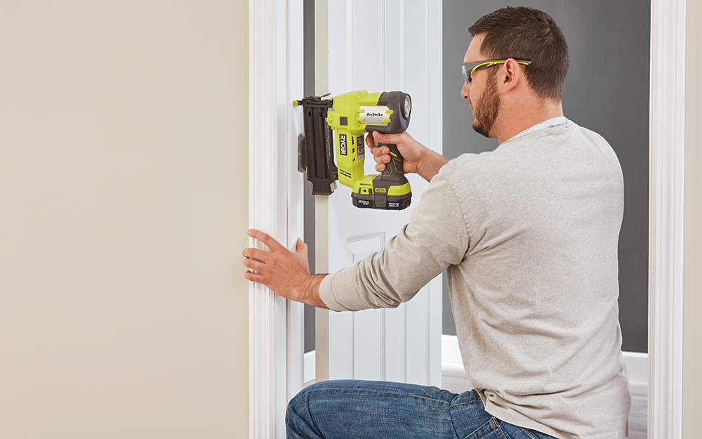 A man securing the center of a door frame with a nail gun.