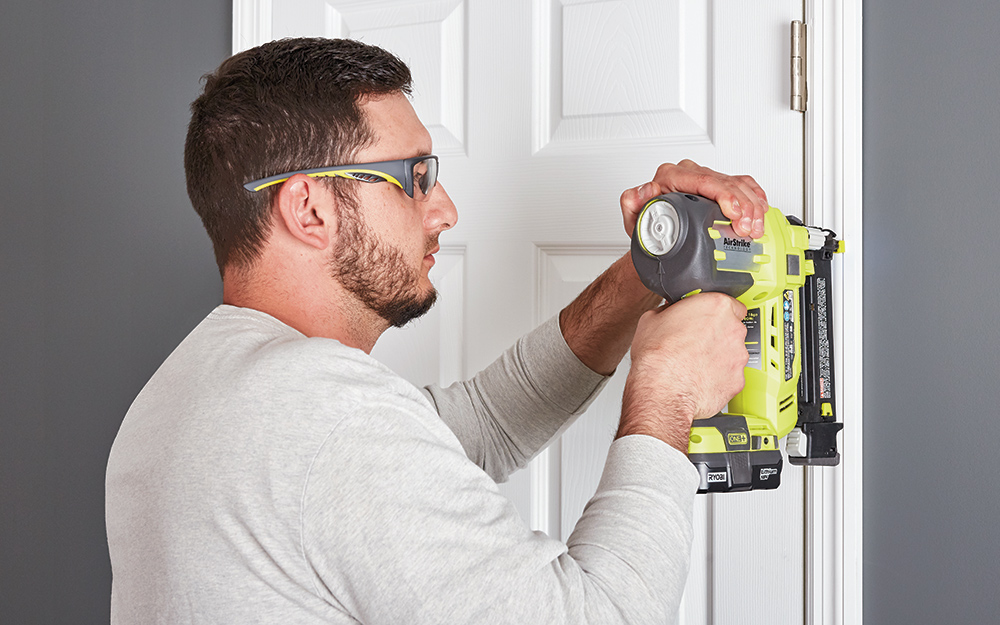 A man securing a white door into place.