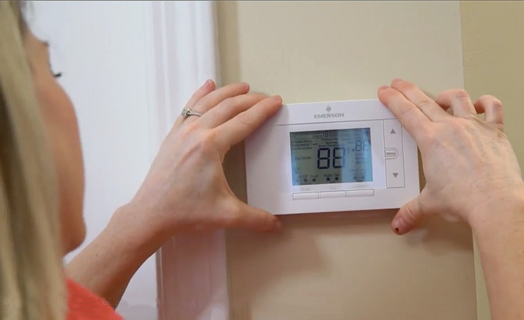 Woman adding face plate to programmable thermostat.