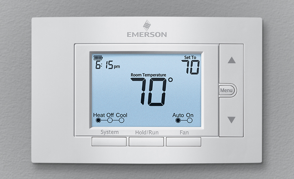 Programmable thermostat installed on gray wall.