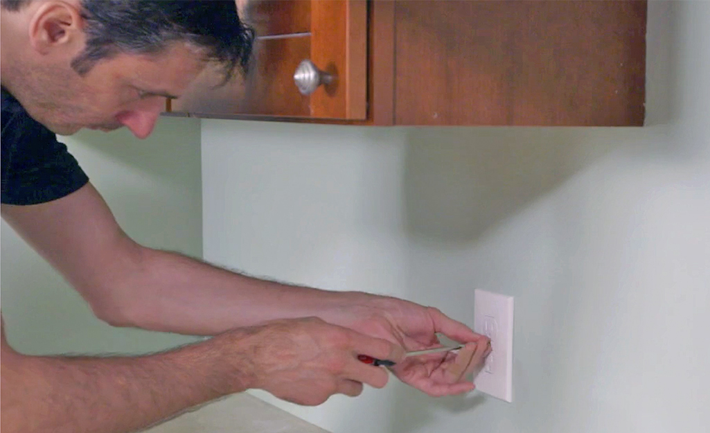 A man removing an outlet cover.