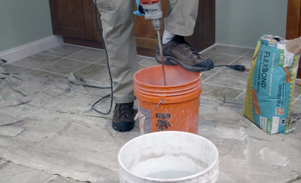 A person pouring water into an orange bucket.