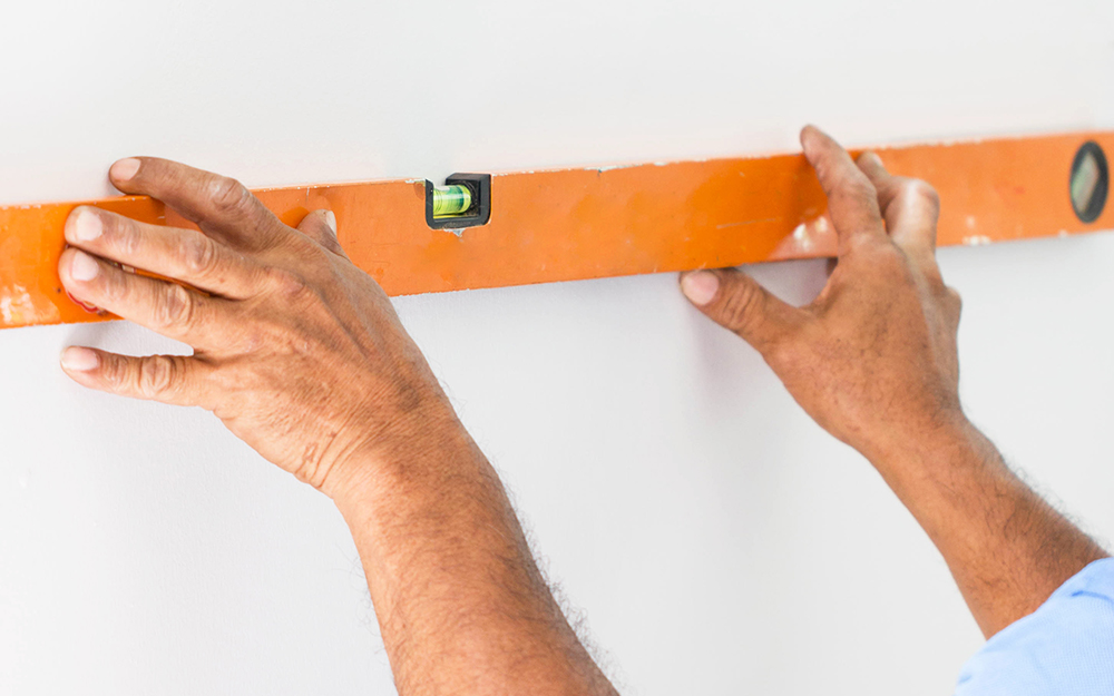 Hands holding a level against a wall.