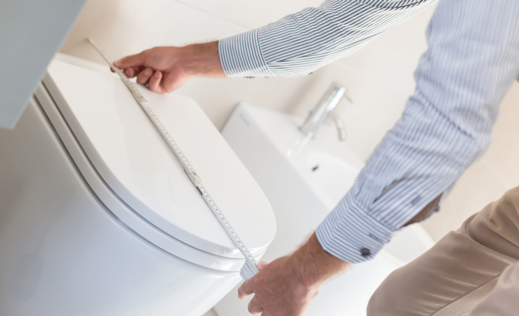 A person measures a toilet seat lengthwise with a tape measure.