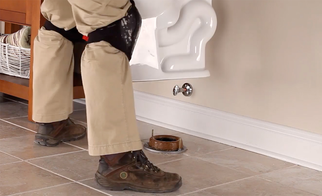 Someone holding a toilet over a flange before placing it down