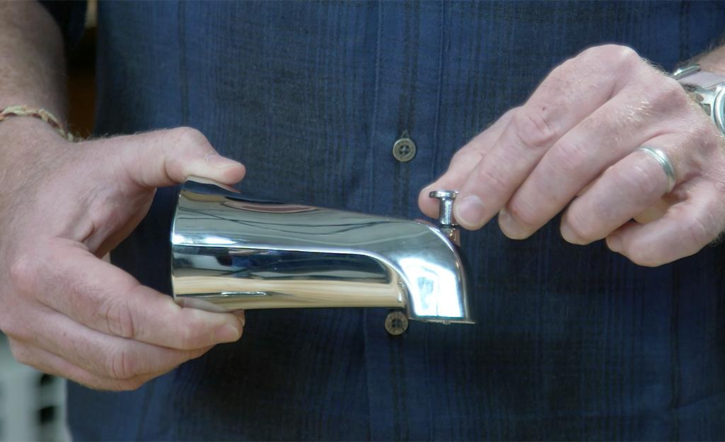 A man holds a tub spout with a diverter valve.