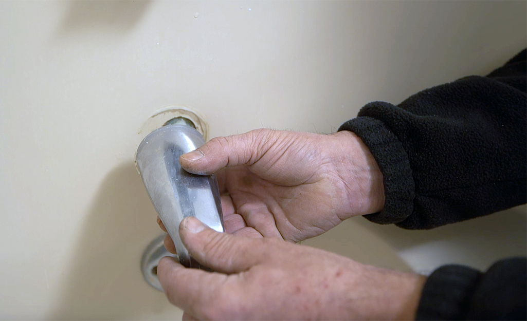 A person removes an old tub spout.