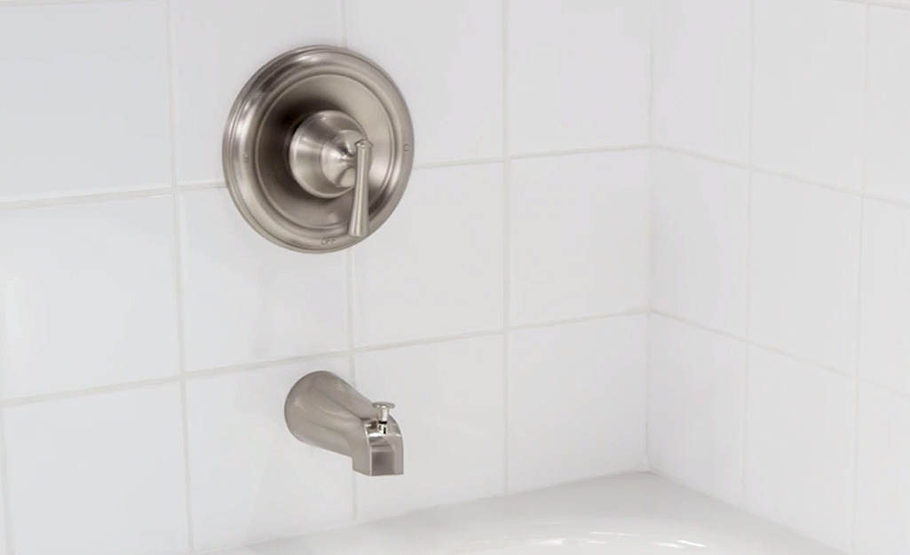 A new tub faucet and shower hardware installed in a white tile bath.