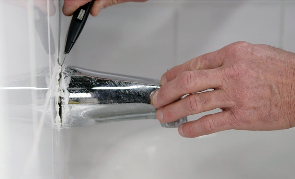 Man loosening an old tub spout with utility knife.