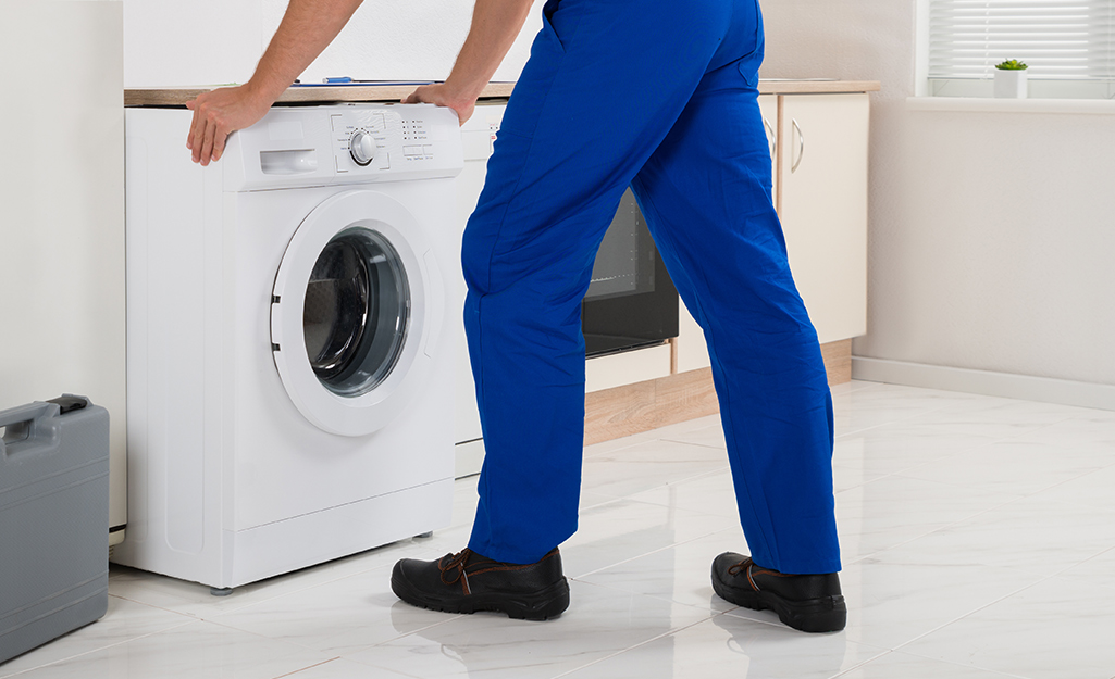 A person pulling a front load washing machine away from the wall.