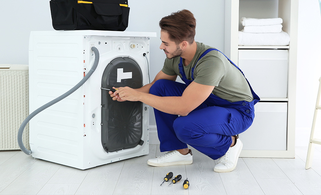 A person unscrewing a bolt on the back of a washing machine.