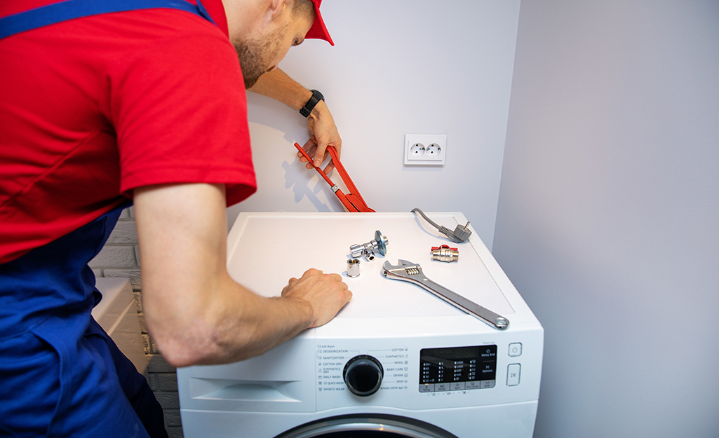 A plumber installing a front load washing machine.