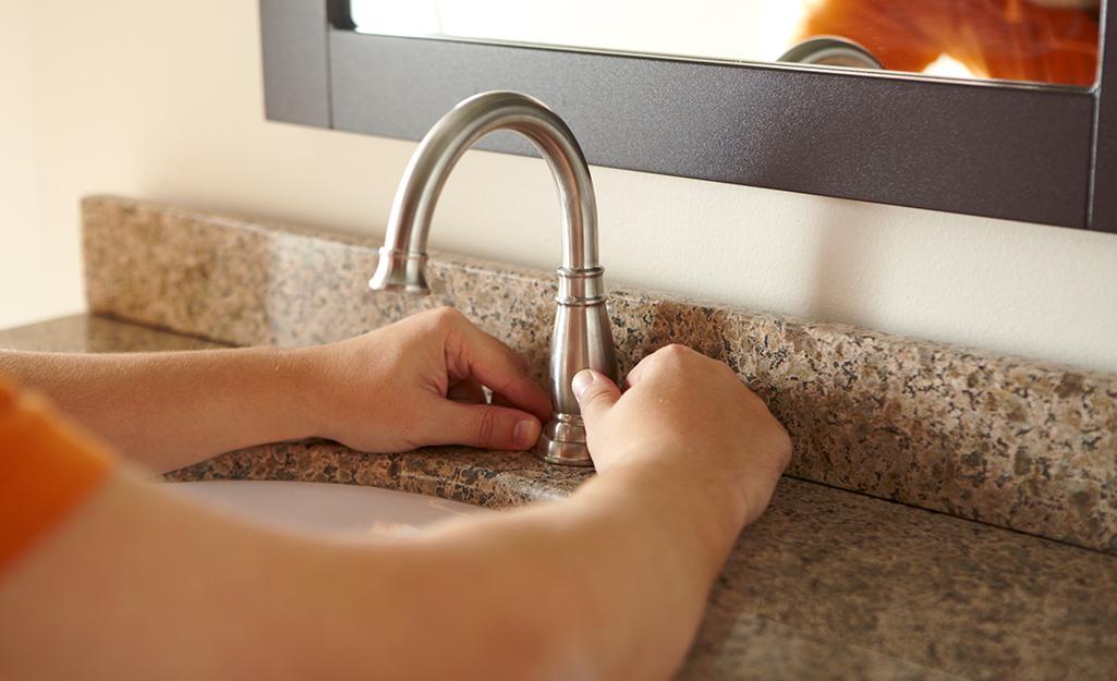 Person centering the faucet spout.