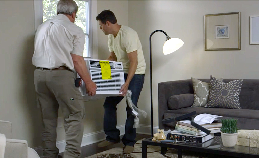 Two people lifting an air conditioner to install it in a window.