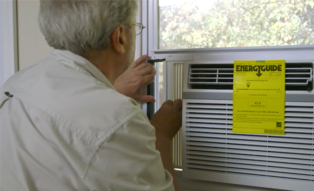 A person extending an AC unit's side panel while installing a window air conditioner.