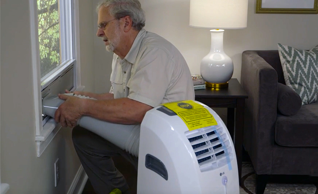 A person attaching a portable air conditioner vent hose to the window panel.