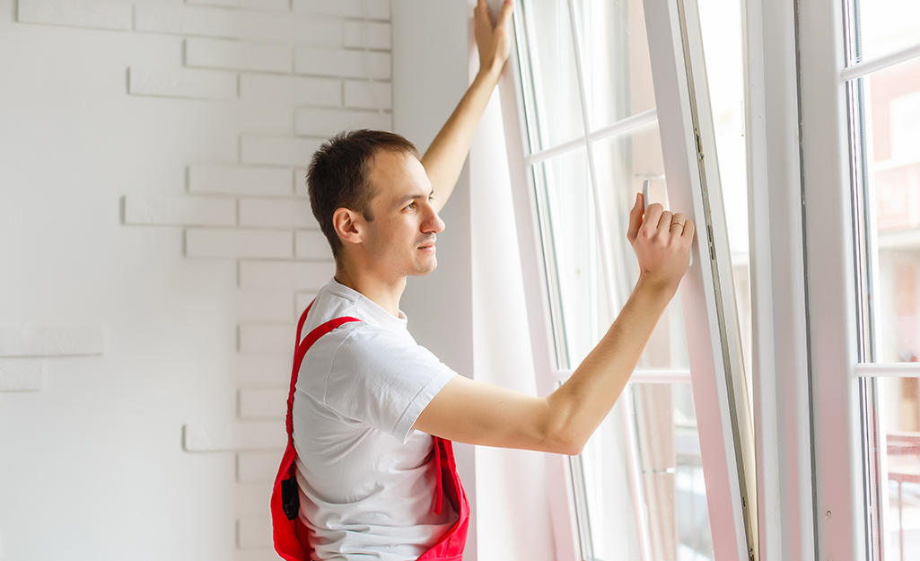A person installing a replacement window.