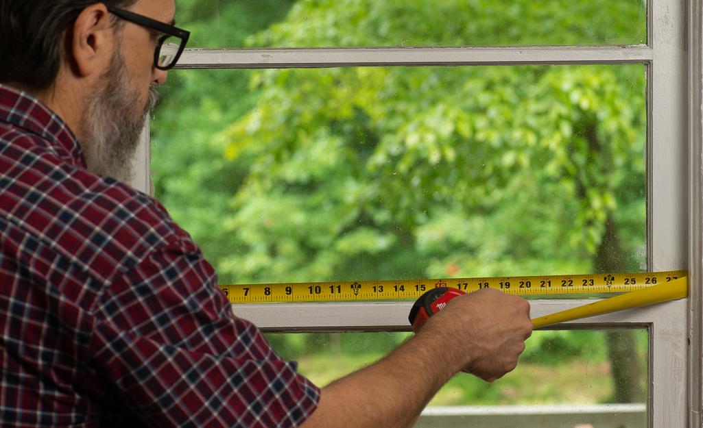 Man measuring the width of a window.